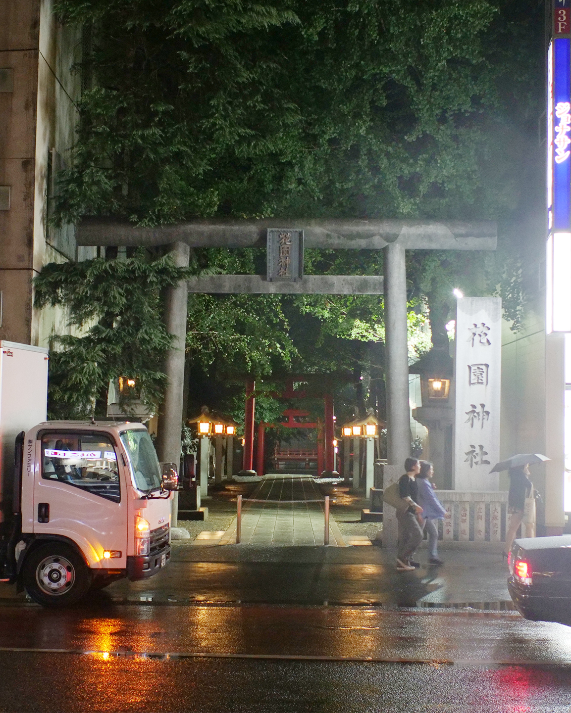 A gateway to a shrine in Tokyo - trees and lanterns sandwiched between an office block and convenience store.